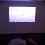 Out Of Blink, Installation shot (video: Jessica Segall, The Thirsty Person, Who Having Found a Spring, Rushes to Drink, Does Not Contemplate Its Beauty (2011), video)