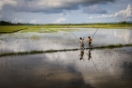Reshma (8) and Ridoy (9) are fishing on the floodwaters after a monsoon. They don't know how to swim. Cox's Bazar. Bangladesh